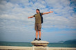 Male runner relaxing after training while standing on stone rock with hands raised against sky background with copy space area for your advertising, fit men celebrating achievement with hands raised
