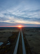Aerial view of the Highway in the Prairies during a vibrant cloudy sunset. Taken East of Edmonton, Alberta, Canada.
