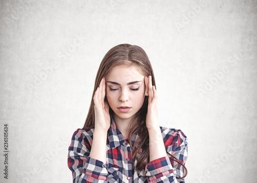 Leinwanddruck Bild Young woman with headache, concrete