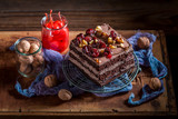 Closeup of chocolate cake with walnuts and cherry - 236506692
