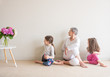 Leinwandbild Motiv Older woman and young children in yoga seated stretch posture - grandmother and grandchildren concept (selective focus)