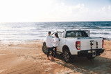 A young couple with a pick up truck on a deserted beach.young couple by pick-up truck parked on beach