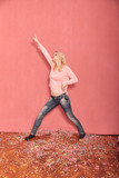 one young woman, standing like a rock star, surrounded with messy confetti fallen on floor, 20-29 years old, long blond hair. Shot in studio on pink background. - 236547801