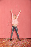 full length shot, one young happy, smiling woman arms outstretched high in air with confetti falling down on floor, 20-29 years old, long blond hair. Shot in studio on pink background. - 236547853