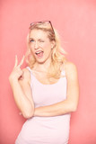 one young woman, 20-29 years old, long blond hair. Shot in studio on pink background. acting funny, two finger peace sign gesturing, wink with eyes. - 236548039