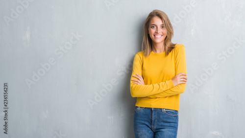 Leinwandbild Motiv Beautiful young woman standing over grunge grey wall happy face smiling with crossed arms looking at the camera. Positive person.