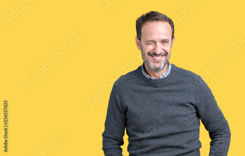 Leinwanddruck Bild Handsome middle age senior man wearing a sweater over isolated background winking looking at the camera with sexy expression, cheerful and happy face.