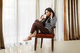 Woman drinking coffee and relaxing on armchair looking out from window - 236558025