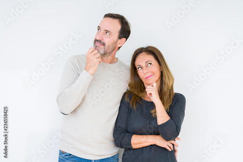 Leinwandbild Motiv Beautiful middle age couple in love over isolated background with hand on chin thinking about question, pensive expression. Smiling with thoughtful face. Doubt concept.