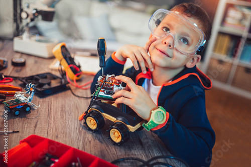 Happy smiling boy constructs technical toy. Technical toy on table full of details