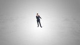 Young businessman standing alone in the middle of an empty space  - 236601007
