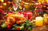 Christmas family dinner. Roasted chicken on holiday table, decorated with gift boxes, burning candles and garlands. Roasted turkey over wooden background - 236601422