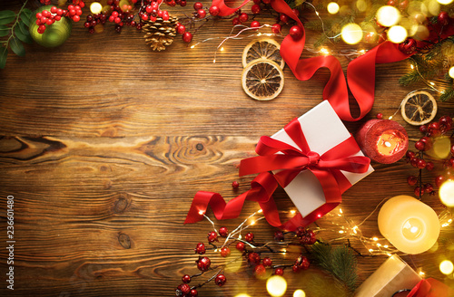 Christmas gift box with red satin ribbon and bow, beautiful Xmas and New Year background with wrapped gift box, candles and lighting garland on wooden table. Top view, flatlay frame