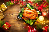 Christmas family dinner. Roasted chicken on holiday table, decorated with gift boxes, burning candles and garlands. Roasted turkey over wooden background. Top view, flatlay - 236601635