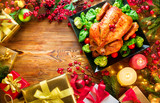Christmas family dinner. Roasted chicken on holiday table, decorated with gift boxes, burning candles and garlands. Roasted turkey over wooden background. Top view, flatlay - 236601841