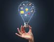 Hand holding light bulb on dark background. New apps concept