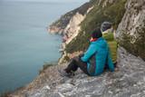 coppia di amiche osservano il panorama sedute sul ciglio della scogliera