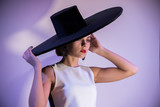 Young attractive woman standing on the background of a white wall in big hat. Purple lighting