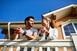 Young amorous couple standing on balcony of their new house and having talk
