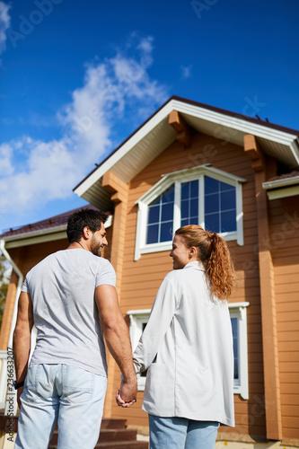 Widok z tyłu nowych właścicieli domu stoi przed nim anad patrząc na siebie