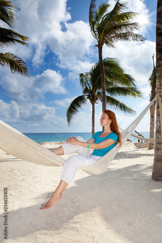 beautiful young woman in a hammock on the beach on background of palm trees and the sea.. - 236635408