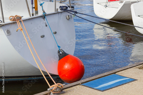Red color fender hangs on the stern of a white white yacht. Blue water. Part of the frame. - 236639031
