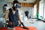 Young tailor with vr headset ironing fabric on board in studio while watching video - 236642050