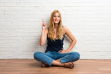 Blonde girl sitting on the floor counting number one sign on white brick wall background - 236643209