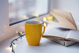 Cup of coffee with books on blurred bokeh background