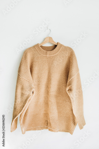 Female woolen sweater on hanger at white wall. Woman fashion clothes concept. - 236646240
