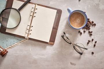 Empty white space in notebook where you can place your text or advertisement. Cup of coffee, airplane, magnifying glasses and glasses on the map. Romantic travel