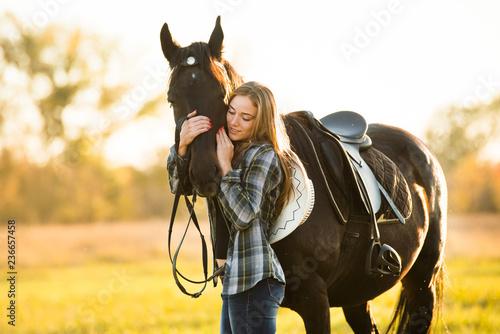 Girl equestrian rider stands near the horse. Horse farm. Horse theme