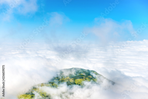 Green mountain peak in white clouds and blue sky - 236659075