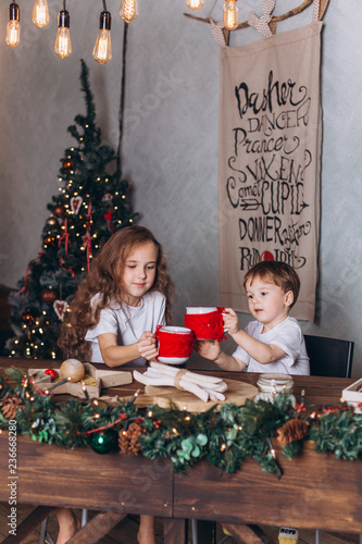 Foto Murales Little kids in christmas decoration with tea at cozy home with colorful new year lights