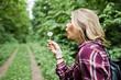 Close-up portrait of a blond girl in tartan shirt blowing dandelion. - 236668698