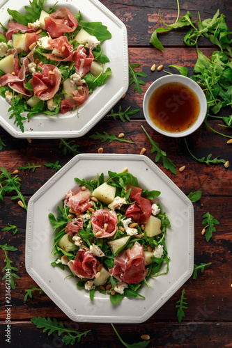 Leinwanddruck Bild Parma ham and melon salad with mozzarella, rocket and pine nuts
