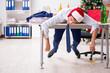 Leinwanddruck Bild - Young handsome employee celebrating Christmas at workplace