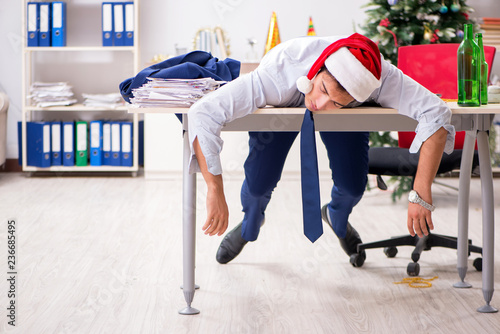 Leinwanddruck Bild Young handsome employee celebrating Christmas at workplace
