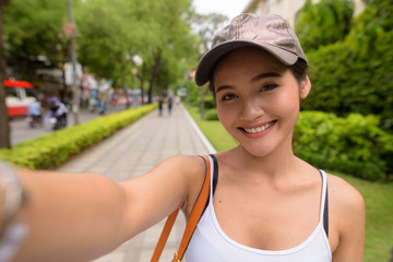 Personal point of view of young beautiful Asian tourist woman smiling and taking selfie