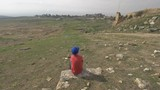 A steadicam shot of a boy sitting on a stone in the green valley in front of picturesque ruins of ancient Hierapolis in Pamukkale. There are no people around, only sun yellowed grass, ruins of ancient - 236720066