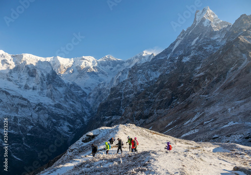 Annapurna region,Nepal - November 15,2018 : group of hikers reaches the mountain peak of Machapuchare. A mountain in the Annapurna Himalayas of north central Nepal