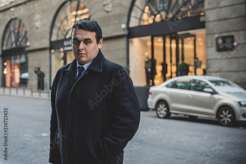 fototapeta na ścianę Worried man with overweight at city streets. Life of businessman or manager, office worker. Plump guy at center in sad mood