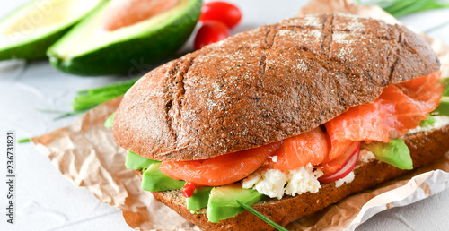 sandwich with avocado and salmon on a light background, green onions and gluten-free grain bread, radishes and tomatoes. concept diet food, copy space, sandwich take away, healthy fast food - 236731821