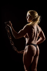 Athletic woman with rusty chain. Attractive fitness lady with long blond hair showing her muscles © Artenex
