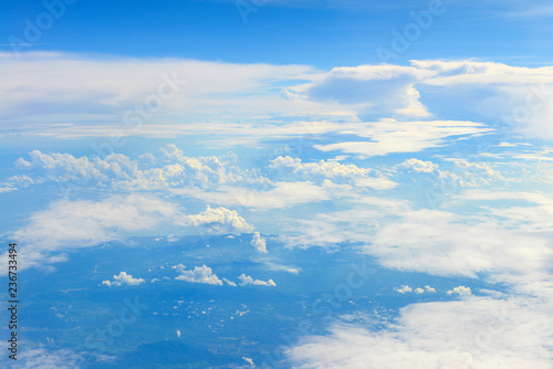 Sun rise in the morning of blue sky above the white clouds and land looking through an airplane window - 236733494
