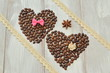 Valentine's Day. Two hearts made of coffee beans with bow tie and decorative flower made of satin, star anise and lace cotton band on light wooden background.