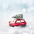 Christmas tree on roof of red toy retro car in snow through snowy winter wonder land with snowfall. Creative Christmas holiday concept. Copy space for your greeting and design. Front view