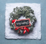 Merry Christmas text lettering. Wreath with green fir branches and red framed sign and Santa hat in snow on blue background, top view . Holiday layout concept.