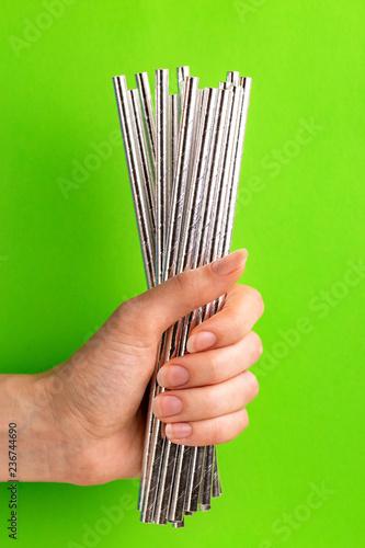 Leinwandbild Motiv Woman is holding siver paper straws in hand
