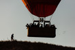 Silhouette of a man taking pictures of a balloon at sunrise